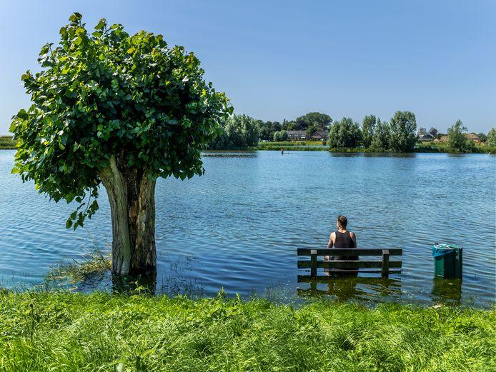 Hoogwater in Tull en 't Waal. Mitchell uit Zeist zit op een bankje dat normaal op het camperveld uitkijkt. Die is nu helemaal onder water gelopen.