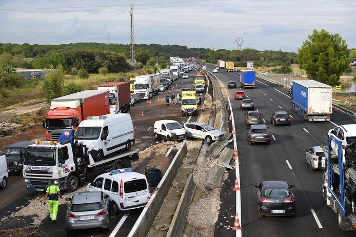 La circulation passe devant des épaves de véhicules sur l'autoroute A9, à Bernis, dans le sud de la France, le 14 septembre 2021, après les fortes pluies qui ont frappé la région.