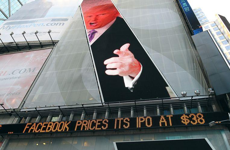 Een foto van Donald Trump wordt geprojecteerd boven een lichtkrant met de waarde van een aandeel Facebook bij de beursintroductie van het bedrijf in 2012.  Beeld AFP