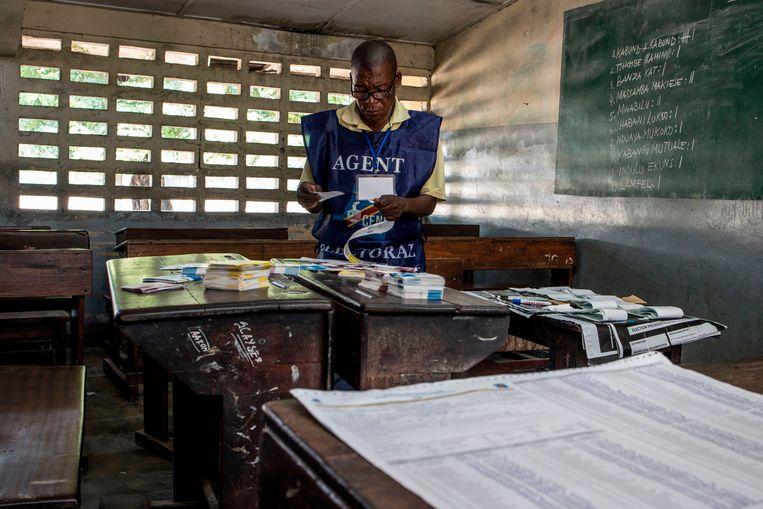 Een man bekijk stembrieven na de verkiezingen in Congo eind vorig jaar. Beeld AFP
