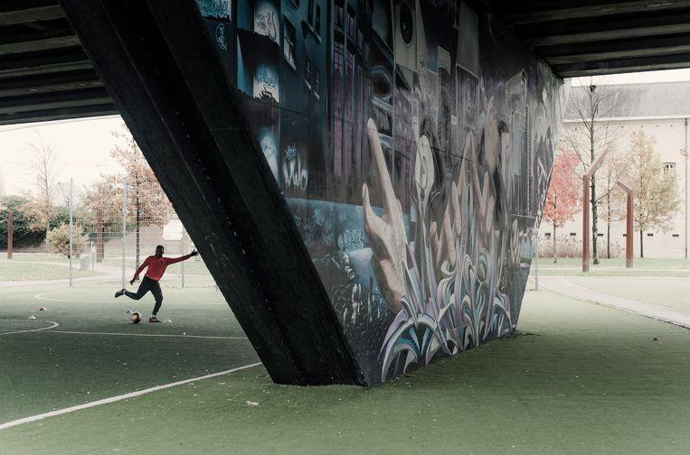Een voetballer op het synthetische veldje onder de Vilvoordse Europabrug. Beeld Karoly Effenberger