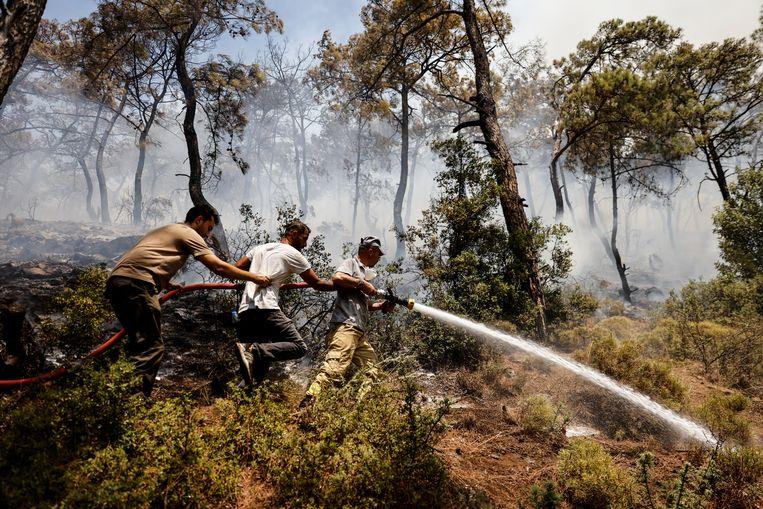 Brandweerlieden en vrijwilligers aan het blussen in de bossen bij Marmaris. Beeld REUTERS