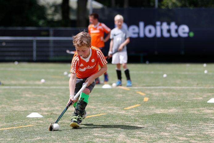 Een jonge hockeyer in actie bij BH&BC Breda in het kidspark dat daar afgelopen zomer tijdens  de Champions Trophy was ingericht.