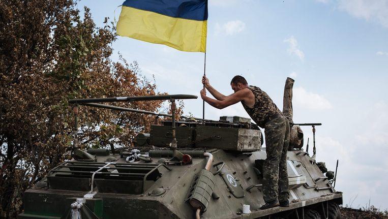 Een Oekraïense militair plant de vlag van Oekraïne op een militair voertuig. Beeld epa