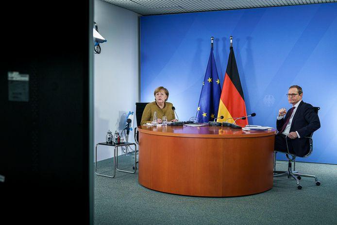 Bondskanselier Angela Merkel (L) en burgemeester van Berlijn Michael Müller die de videoconferentie met de deelstaten voorzat.