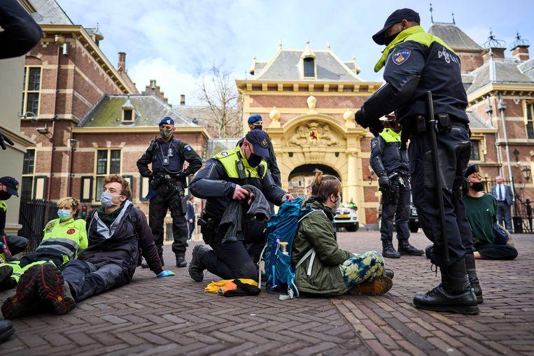 Aanhangers van de actiegroep Extinction Rebellion worden aangehouden bij de ingang van het Binnenhof. Beeld ANP