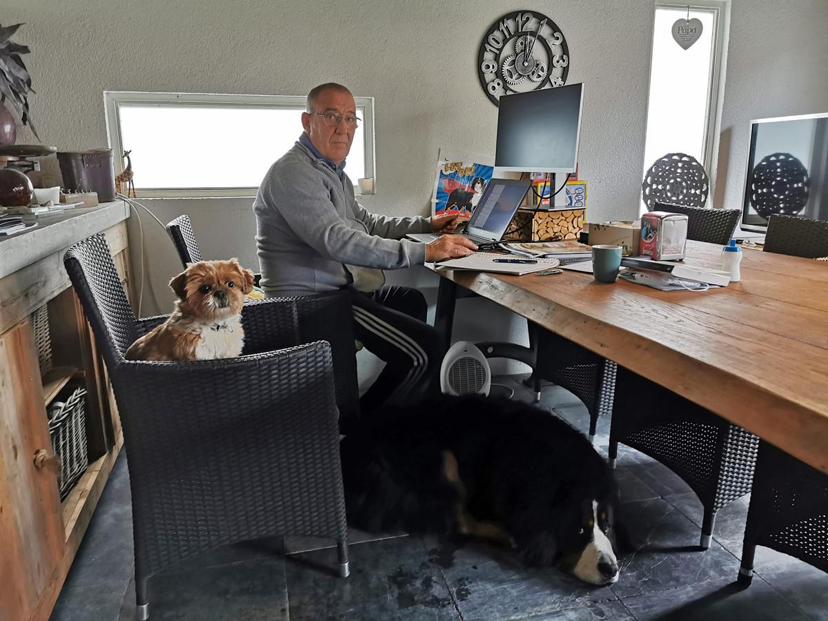 John Smael comfortabel in zijn tuinhuis met zijn honden.
