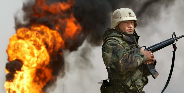 U.S. Army Staff Sergeant Robert Dominguez, of Mathis, Texas, stands guard next to a burning oil well at the Rumayla oil fields March 27, 2003 in Rumayla, Iraq. Several oil wells were set ablaze by retreating Iraqi troops in the Ramayla area, the second largest offshore oilfield in the country, near the Kuwaiti border. Beeld GETTY