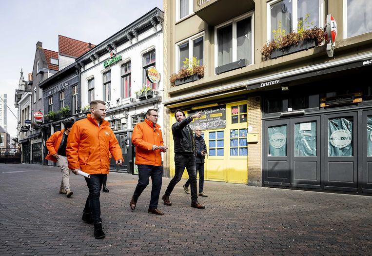 De Mos voert een gesprek met horecaondernemers tijdens de campagne van Code Oranje. Beeld ANP /Remko de Waal