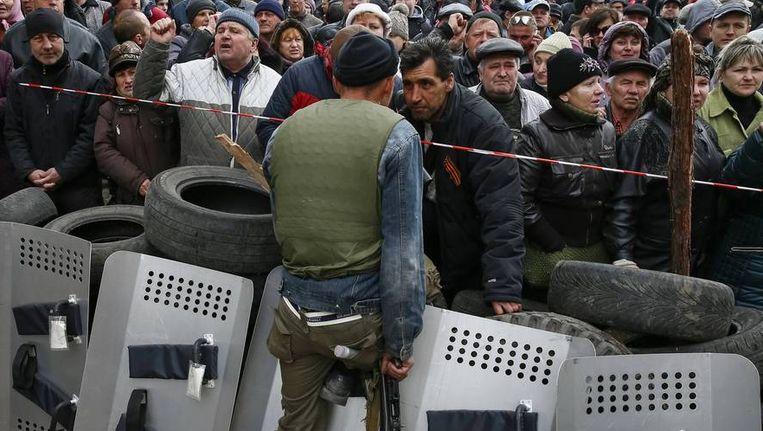 Een pro-Russische militant bewaakt het ingenomen politiebureau in Slavjansk. Demonstranten komen hun steun betuigen. Beeld REUTERS