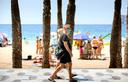 Toeristen lopen met een mondkapje over de boulevard langs het Levante-strand van Benidorm aan de Costa Blanca.