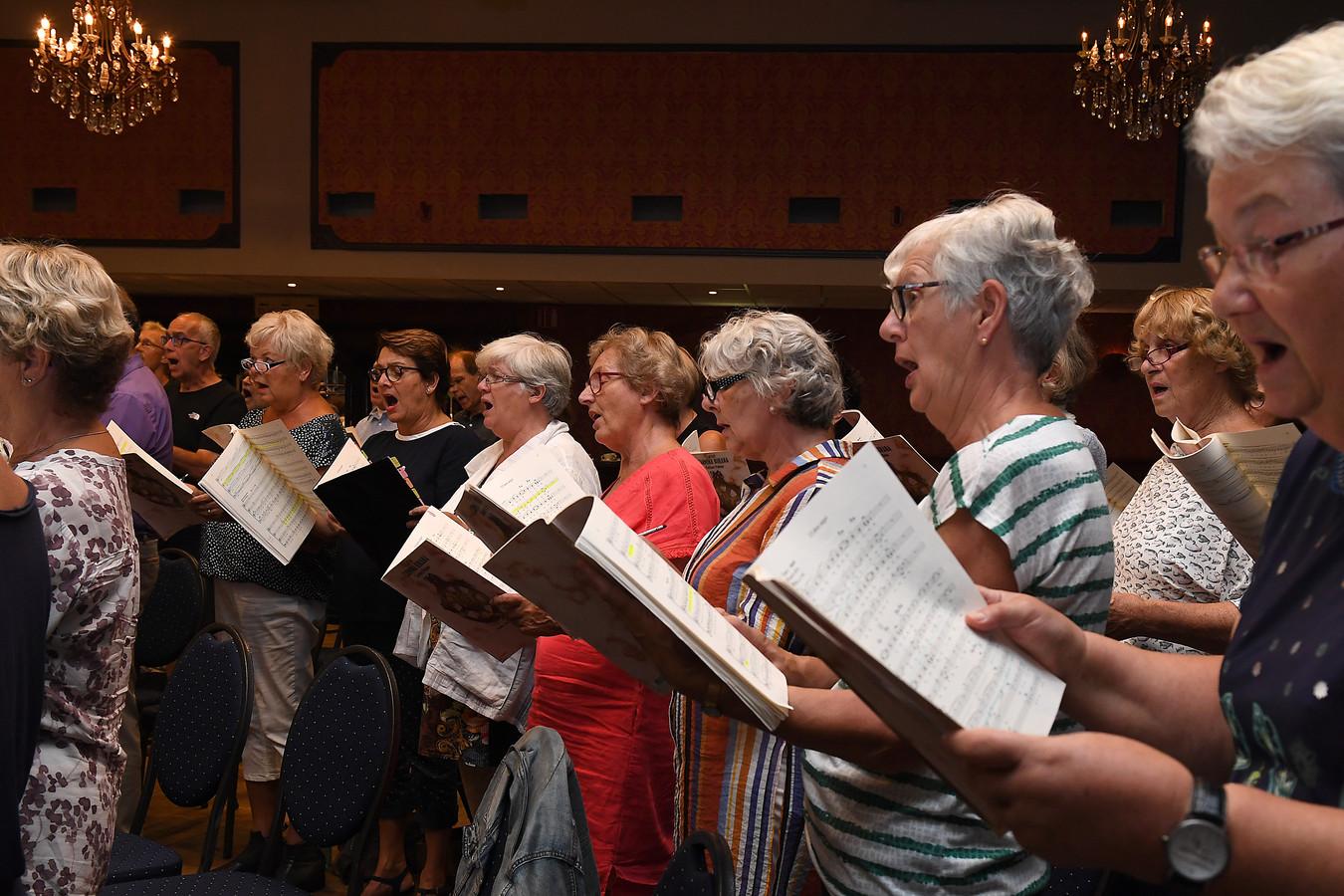 Koorleden repeteren de Carmina Burana voor een optreden in de Cuijkse schouwburg.