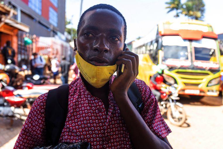 Onesmus Ainebyona belt met zijn vader: hij heeft extra geld nodig om zijn busreis naar huis te kunnen betalen. Beeld Badru Katumba