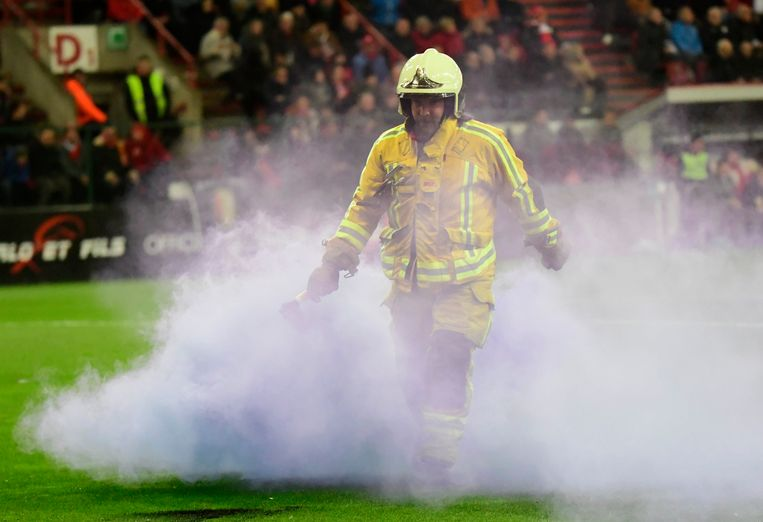 Een brandweerman moet een rookbom, afkomstig van Anderlecht-fans, van het veld halen in Luik. Beeld Photo News