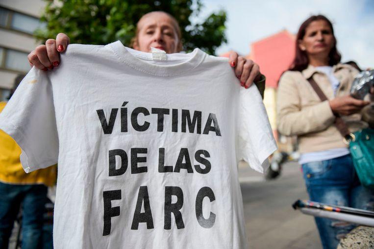 Een vrouw houdt een t-shirt omhoog waarop staat 'slachtoffer van FARC'.