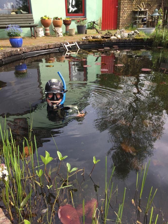 Onderwaterfotograaf in zijn vijver achter z'n eigen huisje in Hattem (Foto Isabella Kolvoort)
