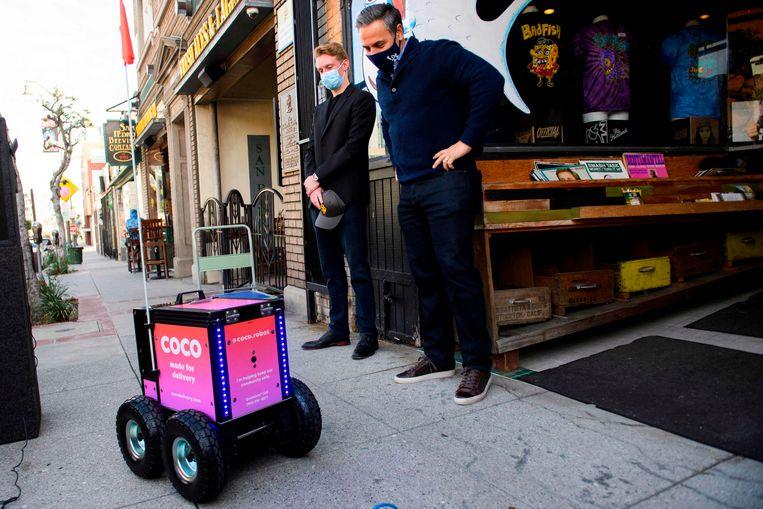Zach Rash, medeoprichter van Coco , en raadslid Joe Buscaino van Los Angeles kijken naar een bezorgrobot. Beeld AFP