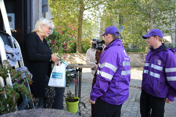 Gemeenschapswachten aan de deur van De Gareelmaeker waar cafébazin Nadine uitleg krijgt over de actie tegen sigarettenpeuken.