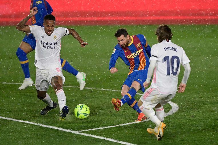 Real Madrid-verdediger Eder Militao (l) en middenvelder Luka Modric proberen een doelpoging van Barcelona-aanvoerder Lionel Messi te voorkomen in El Clasico. Beeld AFP