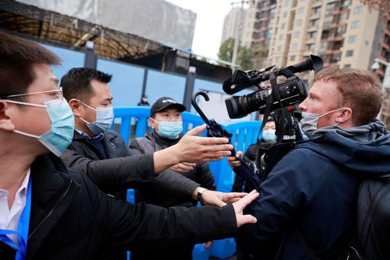 Beveiligingspersoneel houdt journalisten tegen tijdens het bezoek van het onderzoeksteam van de Wereldgezondheidsorganisatie WHO.  Beeld Reuters