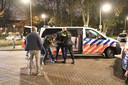 Een van de dertien verdachten wordt na zijn arrestatie gefouilleerd.