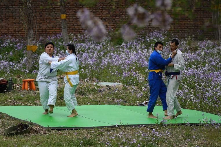 Een groep judoka's in een park in Peking beoefent hun sport met mondkapjes op.   Beeld Getty Images