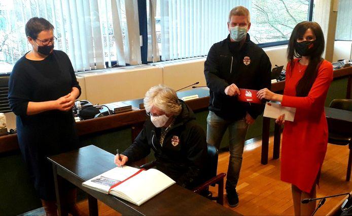 Terwijl HYC voorzitter Van Reeth het Gulden Boek ondertekent, ontvangt secretaris Van Gilsen de cadeaucheques