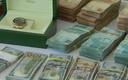 Een van de in beslag genomen Rolex-horloges en cash geld