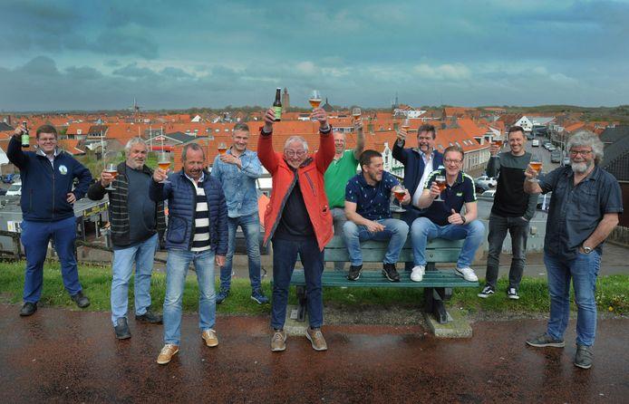 Bram Weststrate, met rode jas, en de andere Westkapelse hobbybrouwers genieten van de Wasschappels tripel.