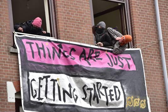 De krakers hangen met sjaals op hun hoofd uit het raam. Op het spandoek staat de leus 'Things are just getting started'.