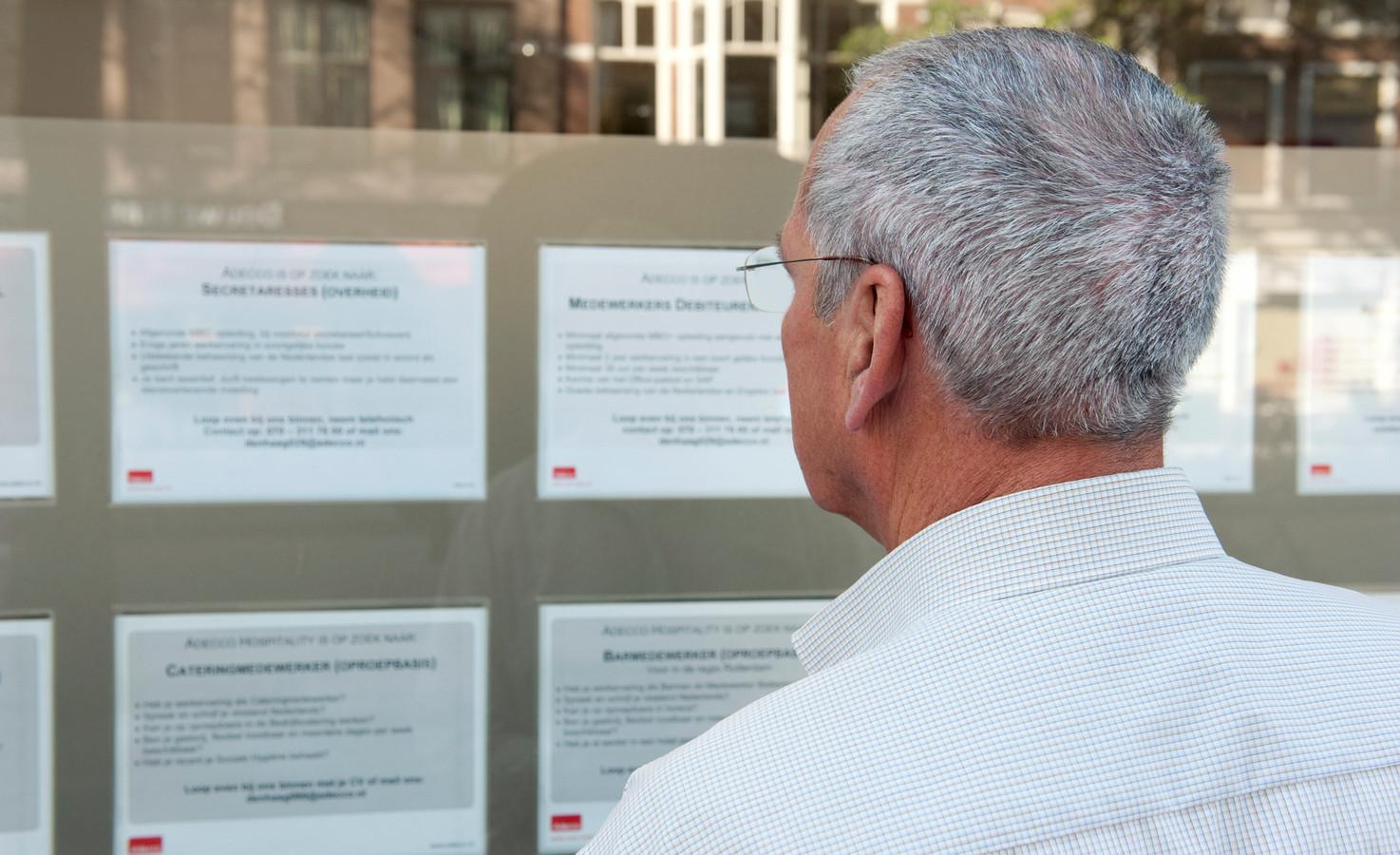 Foto ter illustratie. Een oudere man bekijkt vacatures bij een uitzendbureau.