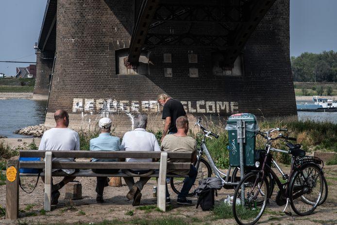 Het eerder deze week bekladde 'Refugees Welcome' op de peiler van de Waalbrug is weer enigszins leesbaar gemaakt