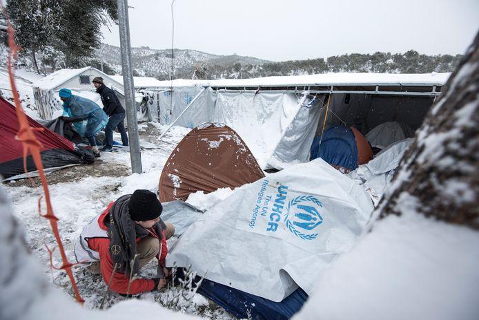 Vrijwilligers van Stichting Bootvluchteling helpen een ingestorte tent weer overeind.