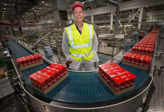 Jaap Wassink bij de verpakkingsmachine van blikjes Coca-Cola.