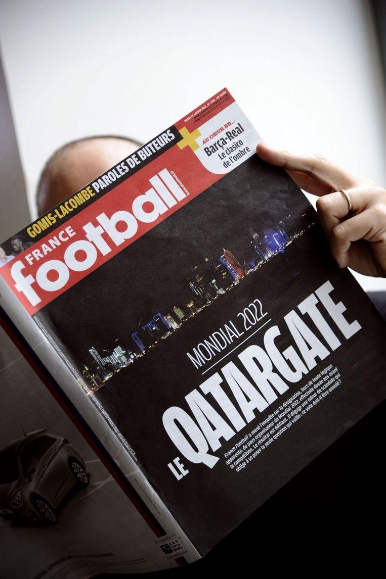 Een man leest een verhaal in France Football eerder dit jaar over de vermeende omkoping die plaats zou hebben gevonden bij de toewijzing van het WK 2022 aan Qatar. Beeld ANP