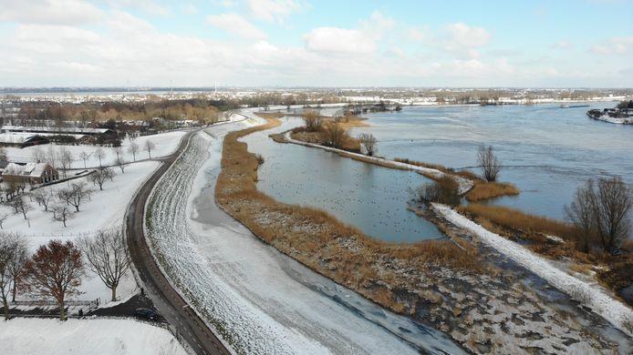 De besneeuwde Lekdijk bij hoogwater.