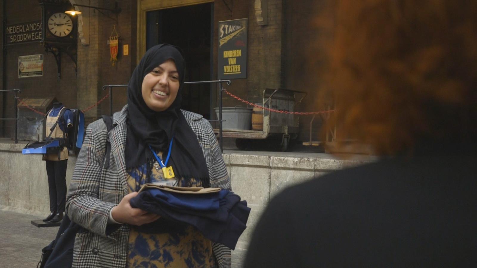 Laila, 'de lach van de NS', overhandigt haar uniform aan een medewerker van het Spoorwegmuseum.