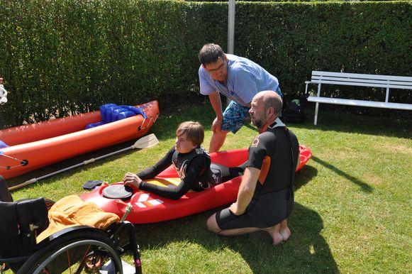 De kinesist en papa Jurgen bekijken of Johannes comfortabel ligt in de bellyac.
