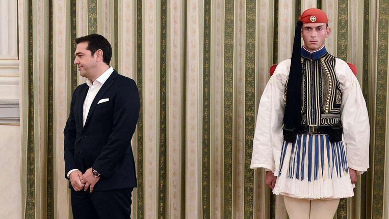 Alexis Tsipras gisteren net voor zijn eedaflegging naast een presidentiële wacht. Beeld AFP