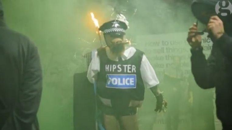 Videostill. Iemand verkleed als politieagent met een varkenshoofd. Beeld The Guardian