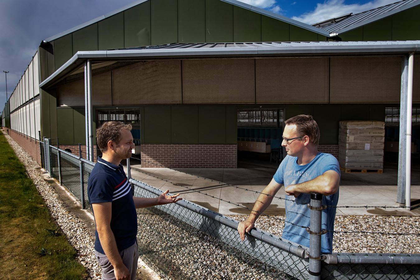Nertsenhouder Martijn van den Boogaard in gesprek met dierenarts Kevin Willems op zijn nertsenfarm, waar een corona besmetting is geconstateerd