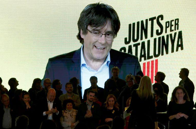 De afgezette Catalaanse minister-president Carlos Puigdemont spreekt partijmilitanten toe via een liveverbinding uit Brussel. Beeld EPA