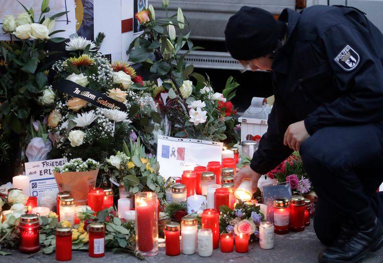 Politieagent steekt een kaars aan om de slachtoffers van de aanslag in Berlijn te herdenken.  Beeld AP