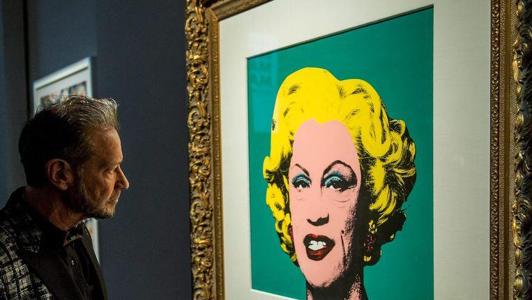 Fotograaf Sandro Miller kijkt naar het werk 'Andy Warhol / Green Marilyn' (1962), 2014 tijdens de opening van zijn expositie Malkovich. Beeld EPA