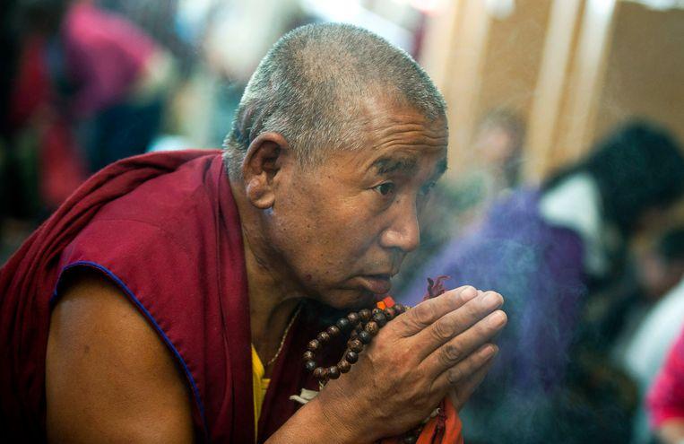 Een Tibetaanse boeddhistische monnik  in India bidt in de richting van het raam waarachter de Dalai Lama een religieuze toespraak houdt in de tempel van Dharmsala, India. Archieffoto. Beeld AP