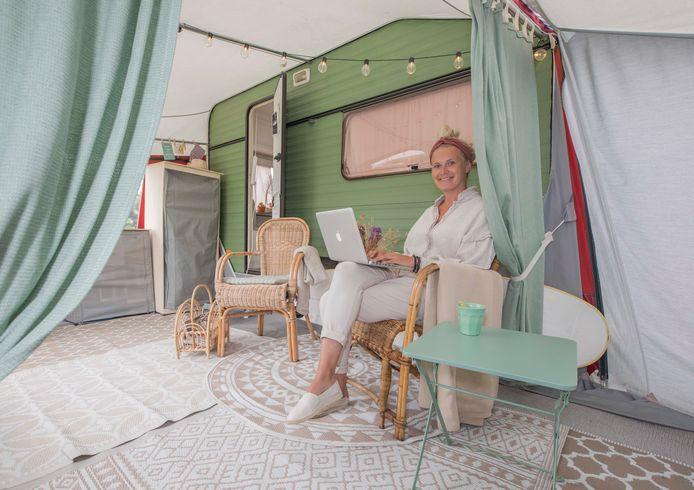 Willemijn Lijnse in de voortent van haar caravan en aan het werk op haar Mac.