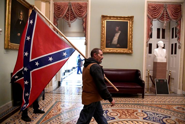Een aanhanger van Trump liep woensdag met de Confederatievlag door het Capitool. Beeld Reuters