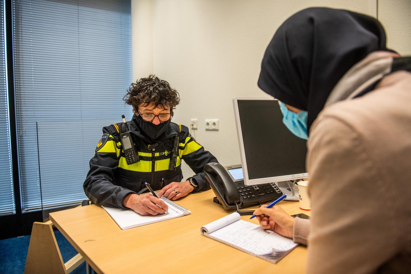 Maryam Amaddaou (voorgrond), specialiste eergerelateerd geweld bij de politie, neemt op  het bureau in Alphen met een collega een zaak door. De politie werkt (vaak) met een checklist eergerelateerd geweld.