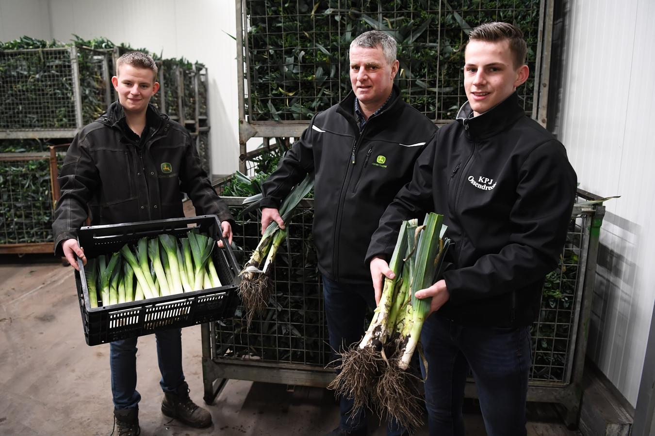 Luc (links), Arnold (midden) en Dirk (rechts) met hun prei. Luc heeft een kist schoongemaakte prei vast, Arnold en Dirk laten zien hoe de prei na het rooien binnenkomt.