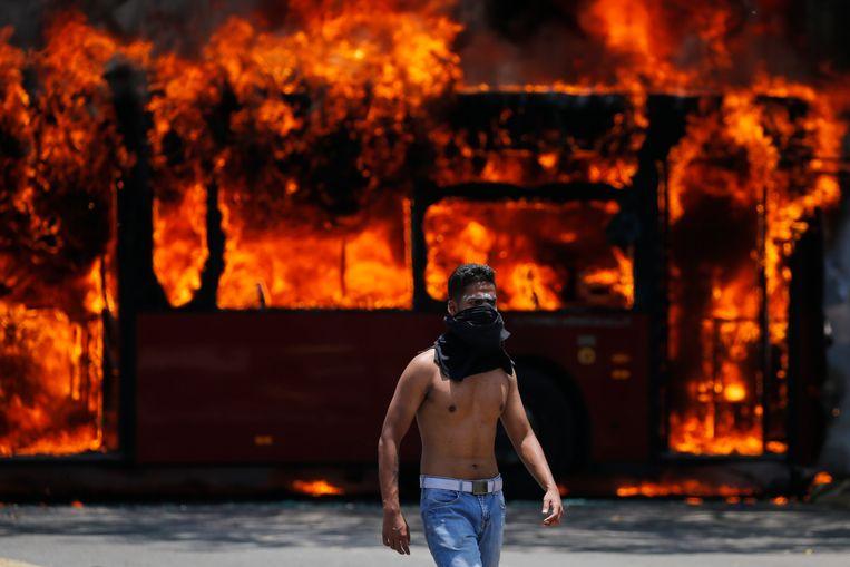 Een demonstrant loopt in Caracas voor een bus langs die in brand is gestoken door demonstranten. Beeld AP